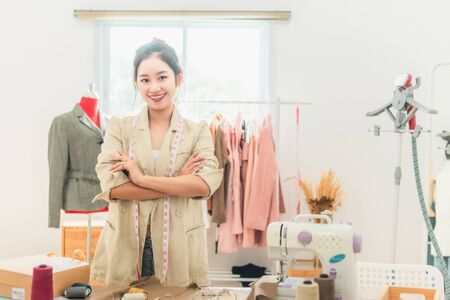 Asian woman designer as a startup business owner in her tailor shop