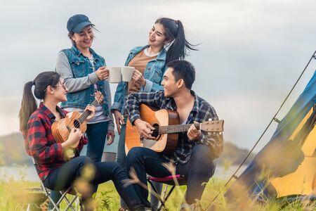 Groupe d'amis asiatiques s'amusant à manger un barbecue en plein air en camping et à jouer de la guitare. Banque d'images