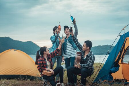 Happy family on a camping trip relaxing by their tent Banque d'images - 131854513