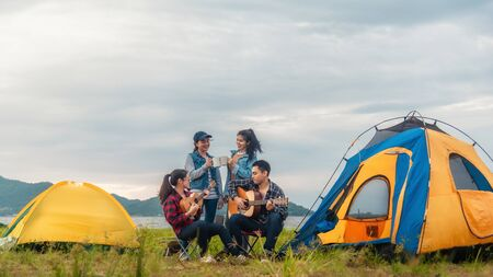 Happy friends playing music and enjoying bonfire in nature Stok Fotoğraf