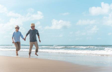 Asian couples, seniors are walking and resting on the beach in the morning.