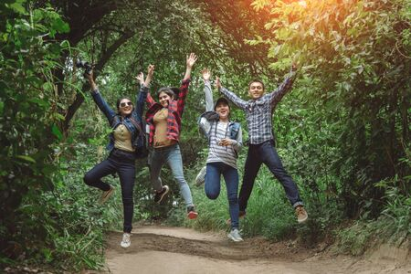 Coworkers Stacking Fists While Standing In Forest On Sunny Day