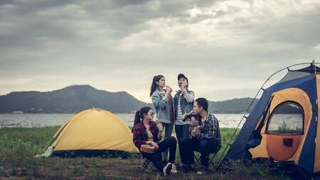 キャンプファイヤー、観光の背景の近くでリラックスバックパッカーのグループ。