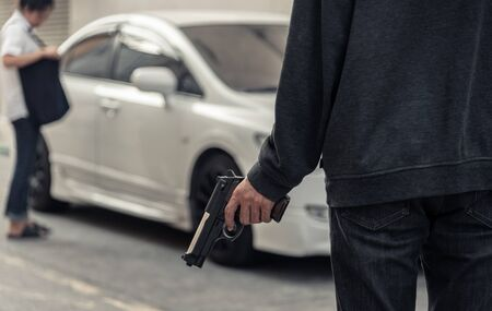 Mujer que roba el bolso por el hombre vestido con camisa a rayas, máscara negra, sosteniendo la pistola. Aparcamiento de coches. Concepto de seguro criminal, trampa, propiedad y vida Foto de archivo