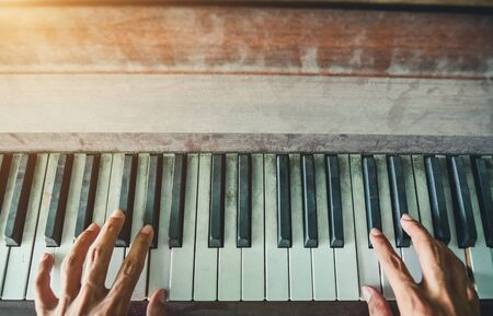 Man's hands playing the Piano. Retro Style. Warm color tones