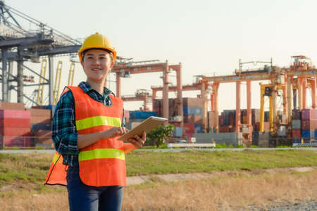 Young Caucasian man and woman worker Check and control loading freight Containers by use radio communication at commercial shipping dock felling happy.