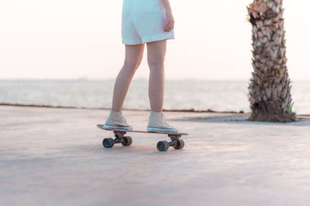 Surf Skate,women playing extreme sport with four wheels on board sliding on street beach summer background Foto de archivo