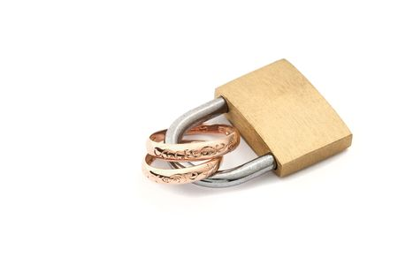 constancy: isolate padlock with golden wedding rings