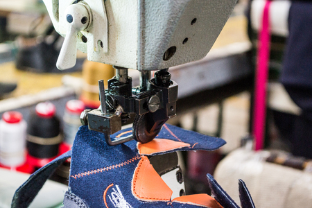 Horizontal photo in color and shallow depth of field about an industrial sewing machine