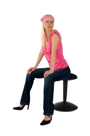 blonde in a pink blouse and blue jeans on a chair