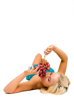 blonde girl in blue with grapes Stock Photo