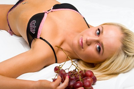 blond in underwear lays on the white with grapes