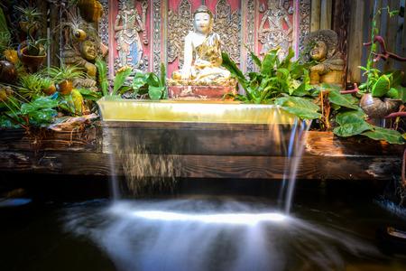 koy: Buddha waterfall over koi pond Stock Photo
