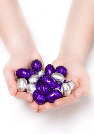 Pair of hands holding purple and silver Easter eggs