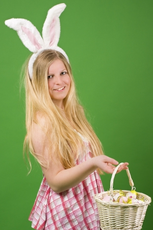 Young blonde woman in a pink dress presenting Easter eggs in a basket Stock Photo