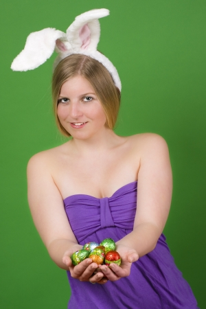Young blonde woman in a purple dress with bunny ears presenting Easter eggs in her hand Stock Photo