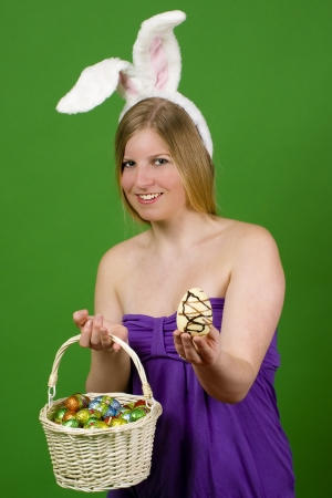 Young blonde woman in a purple dress with bunny ears presenting Easter eggs Stock Photo - 18881225