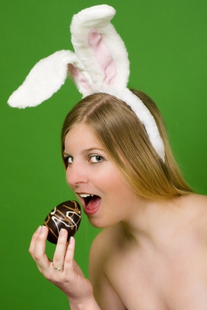 Young blonde woman with bunny ears ready to eat an Easter egg photo