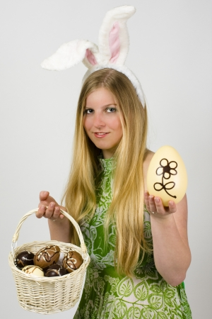Young blonde woman in a green dress with bunny ears presenting Easter eggs Stock Photo