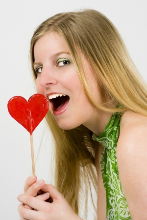 Young blonde woman in a green dress eating a heart of candy Stock Photo - 18881229
