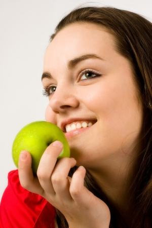 Beautiful young woman in red dress is about to eat a green apple