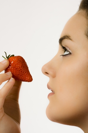 Profile of a beautiful face of a young woman eating a strawberry
