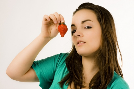 Beautiful young woman in green dress is showing a strawberry in front of her face Stock Photo - 18881545