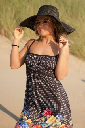 Beautiful youn woman in a black dress wearing a black hat in the dunes Stock Photo - 19609710