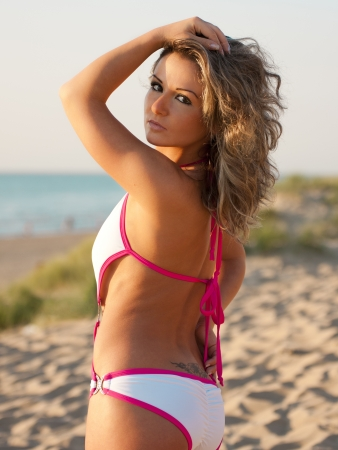 Woman in pink bathing suit at the beach looking over her shoulder