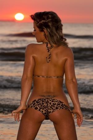 Beautiful young woman posing in the sea at sunset in bikini