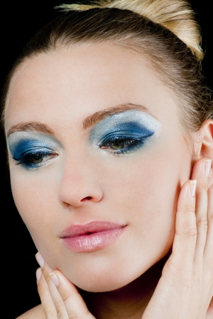 Beautiful young woman with green eyes wearing blue makeup and pink lipstick holding her hands to her face
