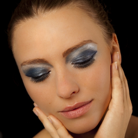 Beautiful young woman wearing blue makeup and pink lipstick holding her hands to her face Stock Photo