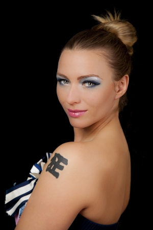 Beautiful young woman with a chinese tattoo wearing blue makeup and pink lipstick