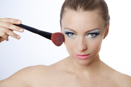 Beautiful young woman holding a brush applying makeup with blue eyeshadow and pink lipstick photo