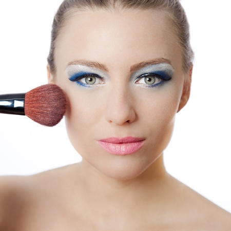 Beautiful young woman holding a brush applying makeup with blue eyeshadow and pink lipstick Stock Photo