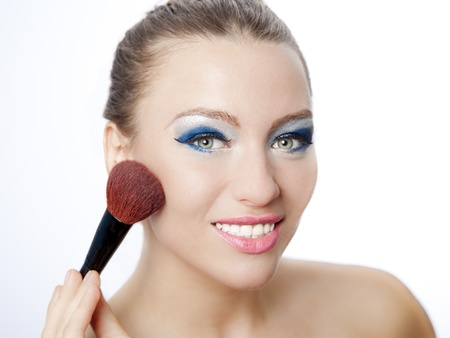 Beautiful smiling young woman holding a brush applying makeup with blue eyeshadow and pink lipstick Stock Photo