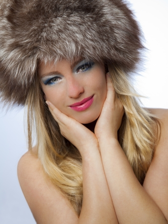 Beautiful young woman with russian hat wearing blue makeup and pink lipstick and holding her hands to her face Stock Photo - 19687109