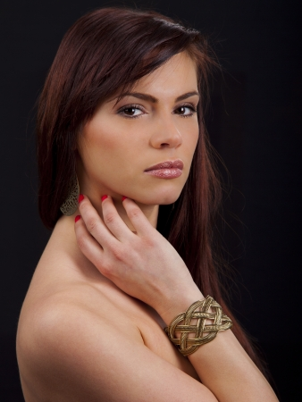 Portrait of a beautiful young romanian woman with her hand to her face wearing a bracelet