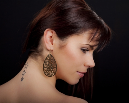 Portrait of a beautiful young romanian woman with star shaped tattoos on her back wearing an earring and pink lipstick