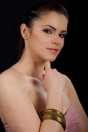 Portrait of a beautiful young romanian woman with her hand to her face wearing a pink dress and a bracelet Stock Photo