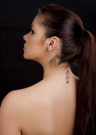 Portrait of a beautiful young romanian woman with star shaped tattoos on her back wearing an earring Stock Photo