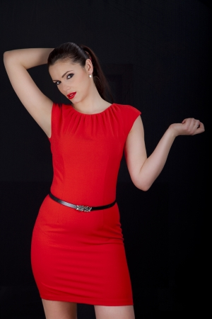 Beautiful young romanian woman posing in red dress with smokey eyes and red lipstick photo