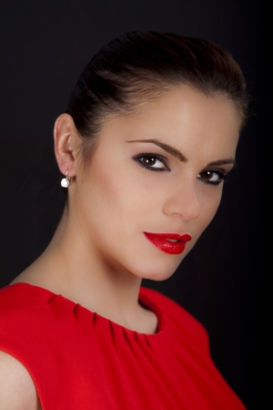 Portrait of a beautiful young romanian woman with smokey eyes wearing a red dress and red lipstick Stock Photo - 19722905