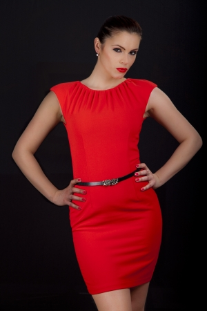 Beautiful young romanian woman posing in red dress with smokey eyes and red lipstick