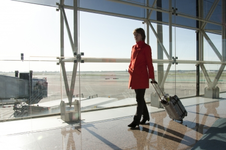 Businesswoman at airport traveling with trolley in red coat Stock Photo - 19856540