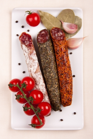 Plate with sausages, tomatoes, garlic, pepper and laurel leaves on a cream colored tablecloth