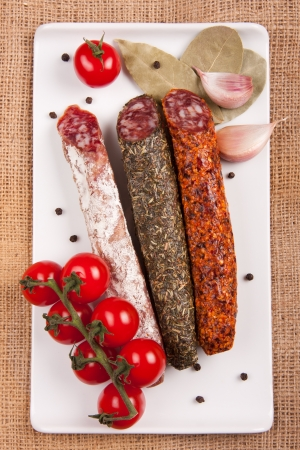 Plate with sausages, tomatoes, garlic, pepper and laurel leaves on a woven tablecloth Stock Photo