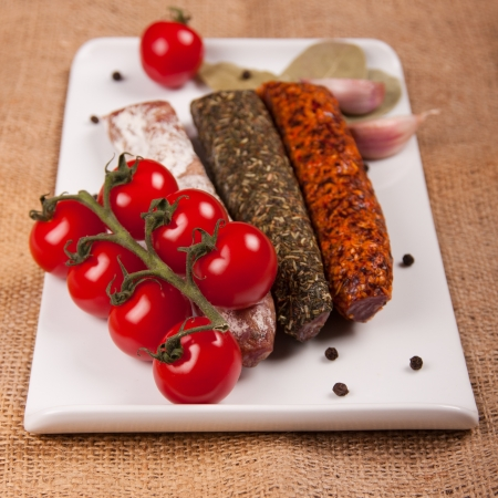 Plate with sausages, tomatoes, garlic, pepper and laurel leaves on a woven tablecloth Stock Photo - 20222735