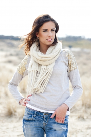 Beautiful young woman wearing a grey shirt, a white scarf and jeans posing in the dunes