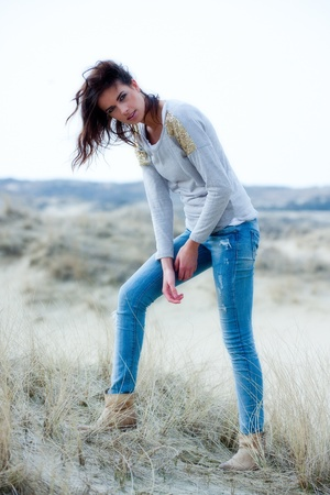 Beautiful young woman wearing a grey shirt and jeans posing in the dunes Stock Photo - 20222865